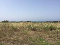leeres Feld bis zum Meer, darunter liegen andere Areale der Stadt